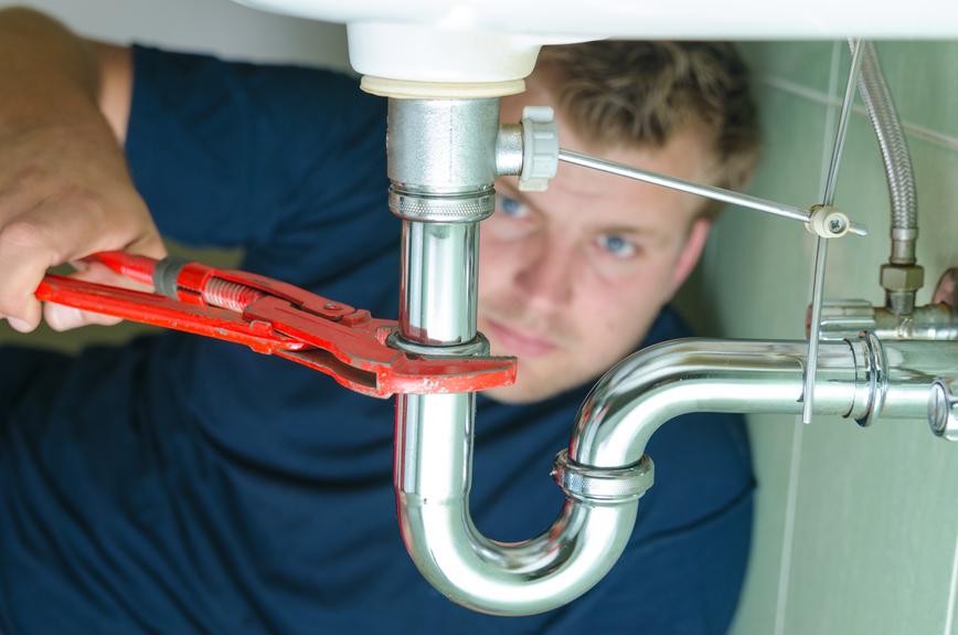Plumber fixing leaky pipe
